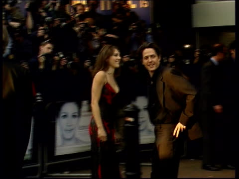 vídeos de stock e filmes b-roll de brits at golden globe awards lib london leicester square hugh grant with girlfriend liz hurley waving to crowd as arriving for premiere of film... - notting hill