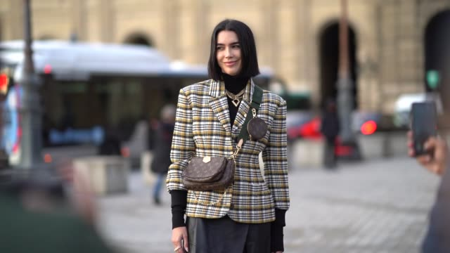 brittany xavier wears a checked pattern blazer jacket a brown vuitton monogram logo bag a vuitton mini bag attached to the shoulder strap golden... - turtleneck stock videos & royalty-free footage