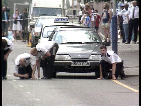 brixton prison report itn lib bv line of police in road with police cordon tape across street ms police searching road ms side policeman crouching on... - seilabsperrung stock-videos und b-roll-filmmaterial
