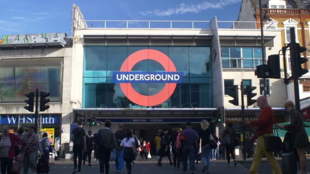 stockvideo's en b-roll-footage met brixton underground station and crowds crossing the road. - advertentie