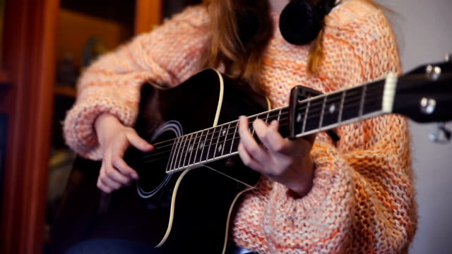 Broad close-up of the hands of a girl playing the guitar