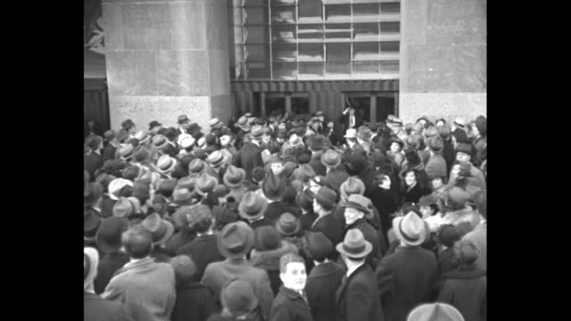 broadcast journalist and war correspondent george hicks wearing top hat with a transmitter on it and holding microphone exits building into huge... - kopfbedeckung stock-videos und b-roll-filmmaterial