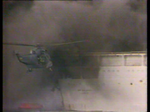 ITV/ITN 40th anniversary POOL Helicopter hovering by bombed ship 'Sir Galahad' MS Boats being rowed