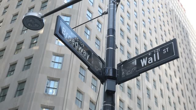 broadway and wall street sign inscription as seen on various buildings, wall st address, downtown in lower manhattan is a significant road and area... - banking sign stock videos & royalty-free footage