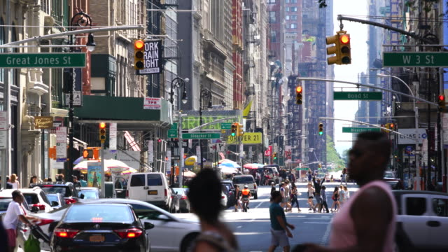 broadway traffic goes through and pedestrians cross the broadway among the rows of buildings at central village at manhattan new york city. - segnale per macchine e pedoni video stock e b–roll