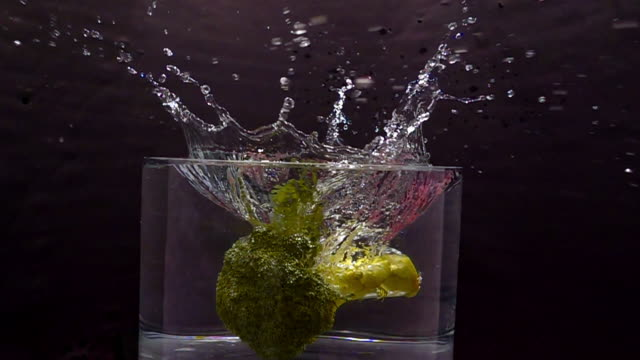 broccoli falls into a bowl of water making a large splash as the camera revolves around it. - david ewing stock videos & royalty-free footage