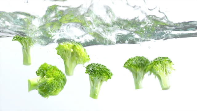 broccoli splashing into water (slow motion) - textfreiraum stock videos & royalty-free footage