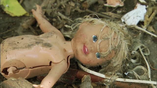 stockvideo's en b-roll-footage met broken, caucasian, legless, blonde doll on branch & dirt covered ground. toy, discarded, trash, gender stereotype toy, litter, child survivor, abuse,... - pop speelgoed