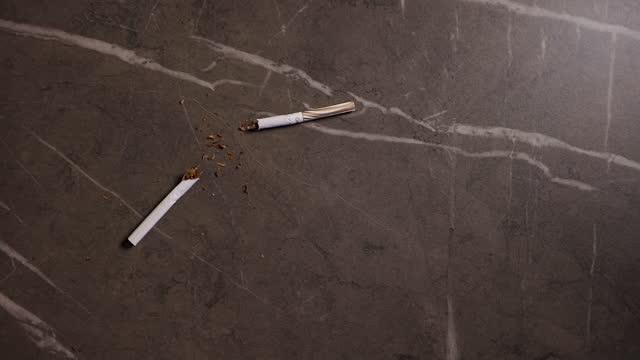 vídeos y material grabado en eventos de stock de broken cigarette with visible tobacco lying on table - modo de vida no saludable