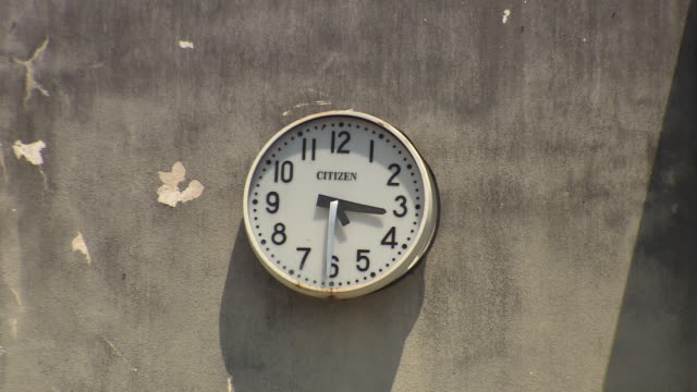 A broken clock hangs on a wall.