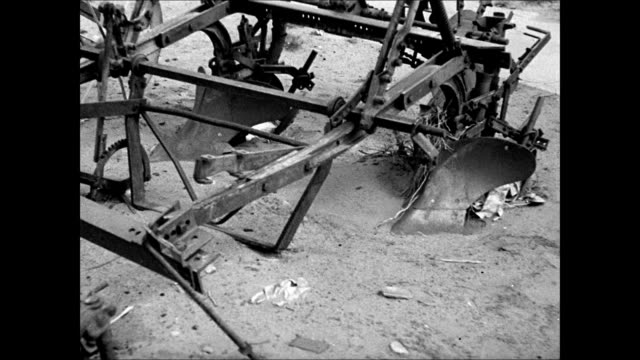 broken windmill w/ 'fairbury' on tail fin vs farm equipment tractors plowing machines sitting in dirt vs sand dunes w/ patches of scrub desert... - dust bowl stock videos and b-roll footage