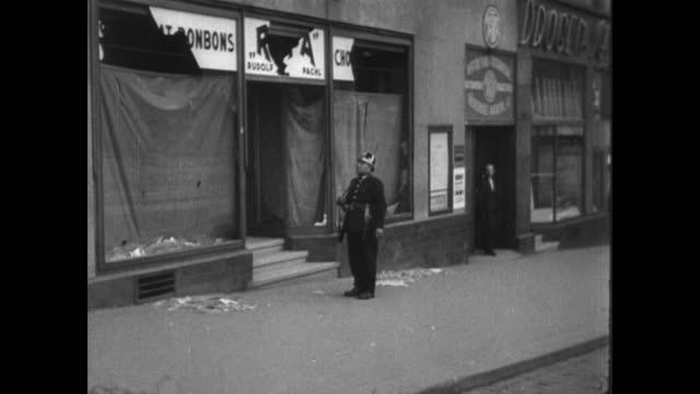 broken window glass, remnants of sudetenland riots / pro hitler graffiti on a wall / people look at poster / upset people in crowd, women crying,... - 1938 stock videos & royalty-free footage