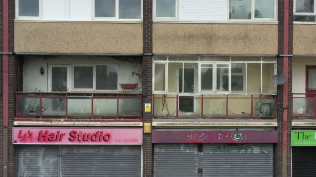 broken windows and shuttered shops blight the landscape in collyhurst on may 28, 2021 in manchester, england. a row of derelict shops and homes in... - 老朽化点の映像素材/bロール