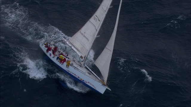 stockvideo's en b-roll-footage met brokenwood cutting through stormy sea: the 54ft yacht sailed by sailors with disabilities in the 2009 sydney to hobart yacht race. skippered by david pescud, australia - jachtvaren