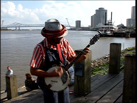 broll footage of a man playing the banjo and singing on a dock in new orleans' french quarter - banjo stock videos & royalty-free footage
