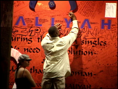 BRoll footage of fans remembering Aaliyah by writing notes on the wall of Tower Records