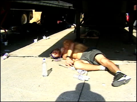 vídeos de stock e filmes b-roll de broll footage of woodstock 99 attendees seeking shade and sleeping under trucks - 1999