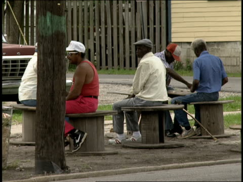 roll men sitting outside playing checkers - 1990年点の映像素材/bロール