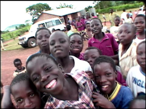 broll of children in africa crowding camera and smiling to it - anno 2002 video stock e b–roll