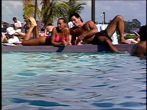 stockvideo's en b-roll-footage met roll of couple at a resort pool in 1990. - zwembroek
