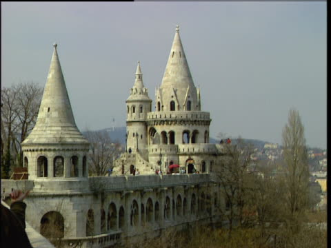 roll of fisherman's bastion tower / zoom out from fisherman's bastion tower, down to an aerial view of neighboring buildings, and then back up. - budapest stock videos & royalty-free footage