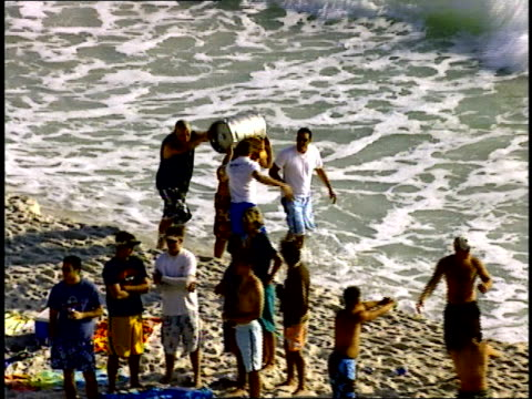 BRoll of Guys Carrying a large keg along a crowded beach