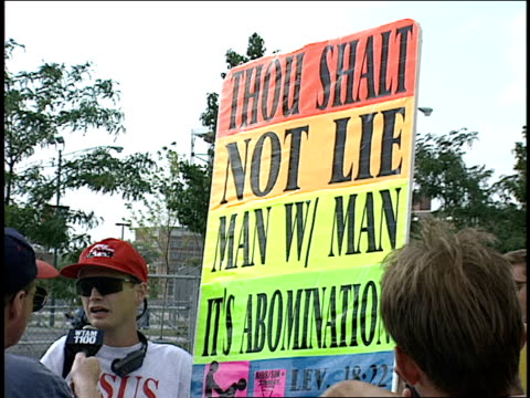 broll of men holding homophobic signs - ホモフォビア点の映像素材/bロール