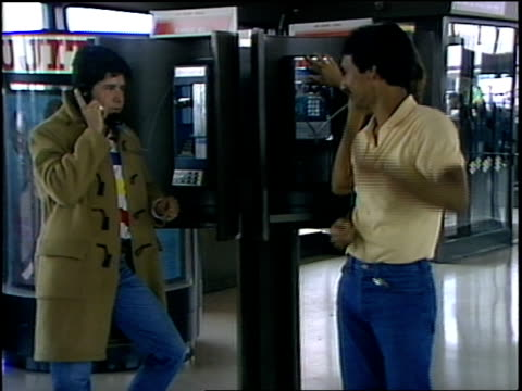 broll of people using payphones in airport in 1986 - pay phone stock videos and b-roll footage