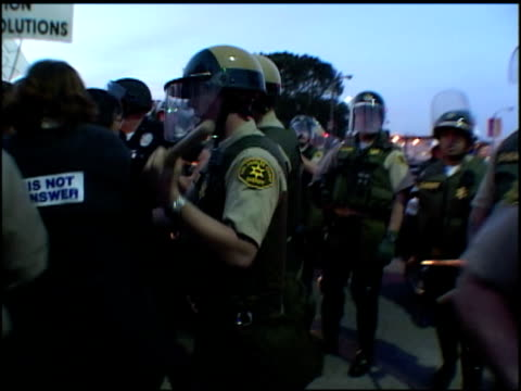 vídeos de stock e filmes b-roll de roll of police pushing protesters with staffs outside federal building in la - maça