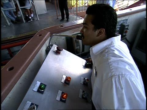 broll of roller coaster conducter welcoming back coaster cars viper roller coaster at six flags magic mountain - サンタクラリタ点の映像素材/bロール
