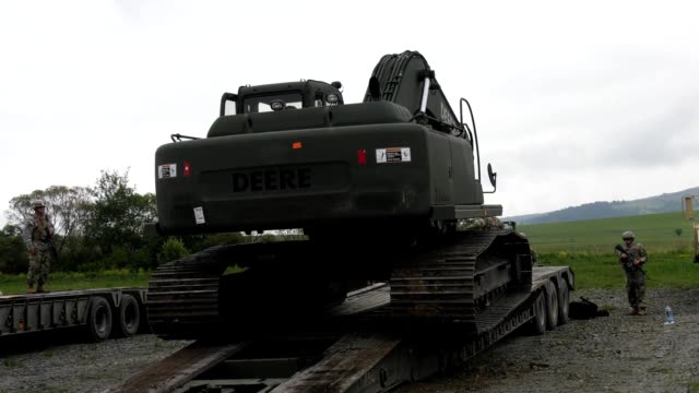 Broll of soldiers from 397th Engineer Battalion 372nd Engineer Brigade 416 Theater Engineer Command loading a Hydraulic Excavator onto a flatbed...