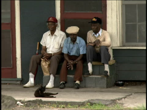 broll of three men sitting outside barber shop - barber shop stock videos and b-roll footage