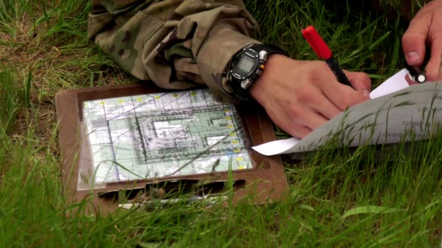 Broll of US Army soldiers conducting land navigation exercises using paper maps compasses and other tools May 16 2018