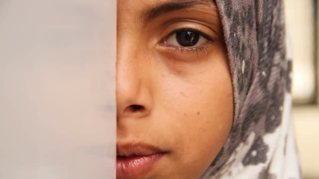 roll portrait of a young girl's face at a refugee camp in sahban. she was displaced due to the battle of amran. - yemen stock videos & royalty-free footage