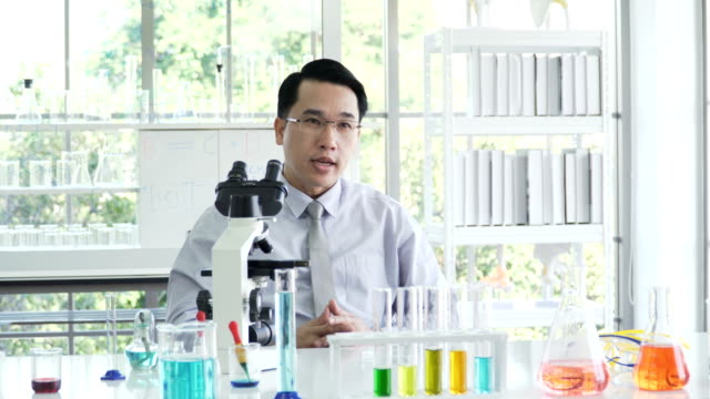 B-roll shot: medical researcher talking with someone in his laboratory