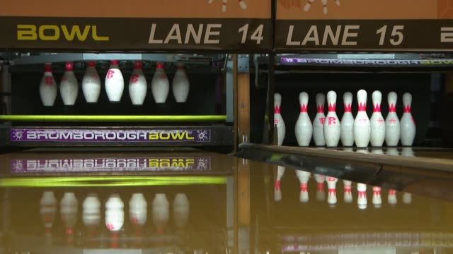 merseyside wirral birkenhead bromborough bowl bowling alley int various of bowling alley staff in protective masks wiping down bowling balls /... - rubbing stock videos & royalty-free footage