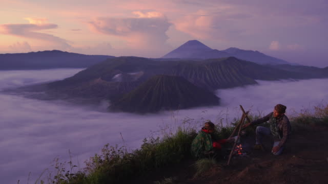 16-04-2018 : bromo tengger semeru national park, indonesia : 2 local indonesian doing campfire while sunrise with mt.bromo in background - tengger stock videos & royalty-free footage