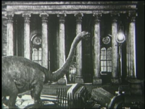 b/w 1925 brontosaurus by building watches people run in london street at night - 1925年点の映像素材/bロール
