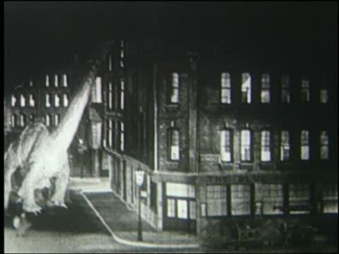 b/w 1925 brontosaurus jumps in pain by building in london at night - 1925年点の映像素材/bロール
