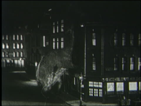 vidéos et rushes de b/w 1925 brontosaurus knocks down building in london at night - destruction