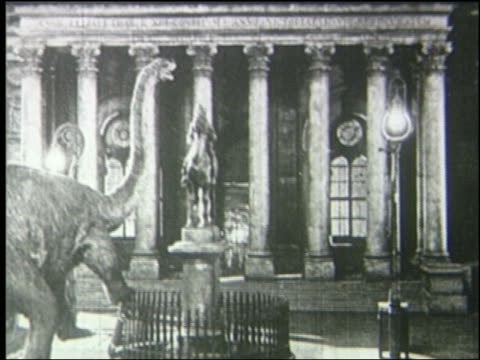 b/w 1925 brontosaurus knocks over statue in front of building in london at night - 1925 stock videos & royalty-free footage