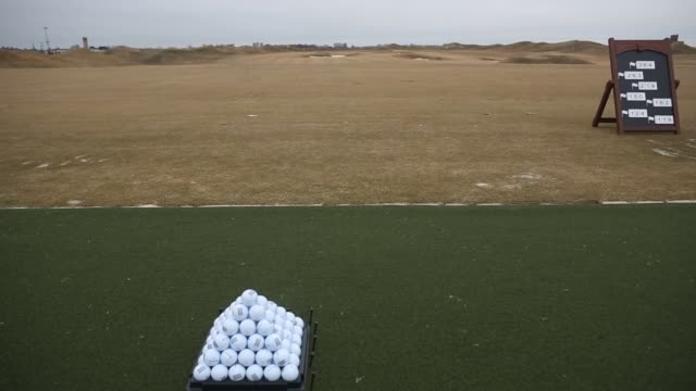 bronx, new york, u.s. march 30th, 2015. photographer: victor blue, a pyramid of golf balls sits on a rack on the ground of the driving range at the... - golf links stock videos & royalty-free footage