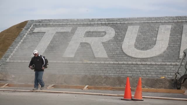 bronx new york us march 30th 2015 photographer victor blue close up shots of stone masons or construction workers building a trump links sign near... - links golf stock videos & royalty-free footage