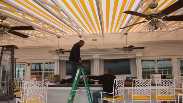 bronx, new york, u.s. march 30th, 2015. photographer: victor blue, exterior shots of construction workers setting up a tent for a banquet on the... - golf links stock videos & royalty-free footage