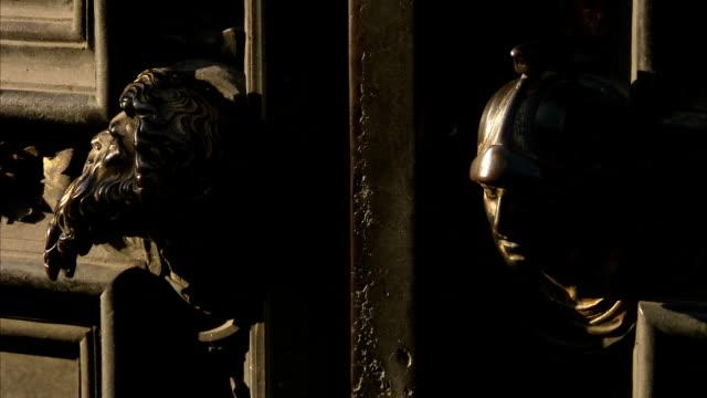 vídeos y material grabado en eventos de stock de bronze heads decorate double doors in florence, italy. available in hd. - bronceado