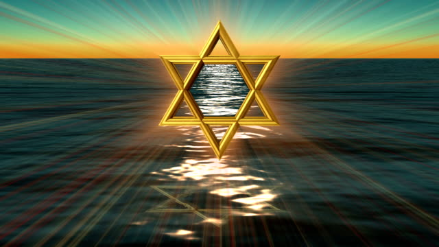 a bronze star of david in front of water. - star of david stock videos and b-roll footage