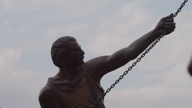 Bronze statue entitled, 'Labor' by Matthew Placzek, a worker with a mustache and strong arms, holds a chain with the sky in background.