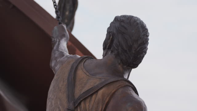 Bronze statue entitled, 'Labor' by Matthew Placzek, back of a strong worker with work shirt and apron, holding a chain; camera zooms to a tighter shot.