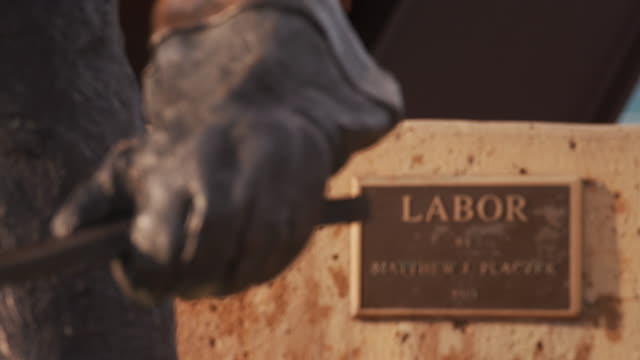 "bronze statue entitled, ""labor"" by matthew placzek, rack focus to gloved hand of a foundry worker at an anvil. - foundry worker stock videos and b-roll footage"