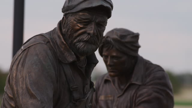 Bronze statue entitled, 'Labor' by Matthew Placzek, two workers, rack focus between a man and a woman, together hold a small vat into the forge to melt the iron.